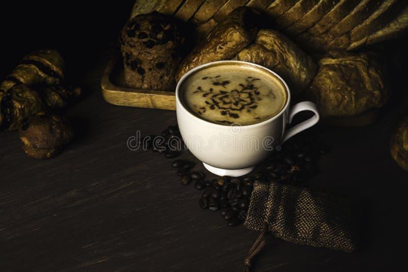 Caffè caldo in tazza bianca con fumo, con i chicchi di caffè e del forno nella borsa della canapa disposta sulla tavola di legno  immagine stock libera da diritti