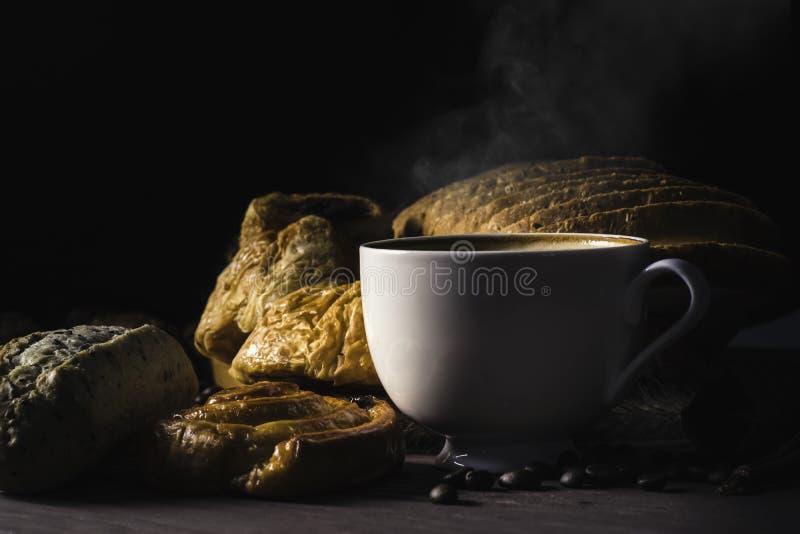 Caffè caldo in tazza bianca con fumo, con i chicchi di caffè e del forno nella borsa della canapa disposta sulla tavola di legno  immagini stock