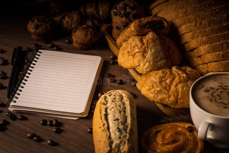 Caffè caldo in tazza bianca, con i chicchi di caffè e del forno nella borsa della canapa, con il taccuino disposto sulla tavola d immagini stock libere da diritti