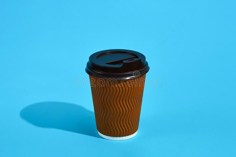 Caffè caldo in tazza di carta marrone con il coperchio nero su fondo blu fotografie stock