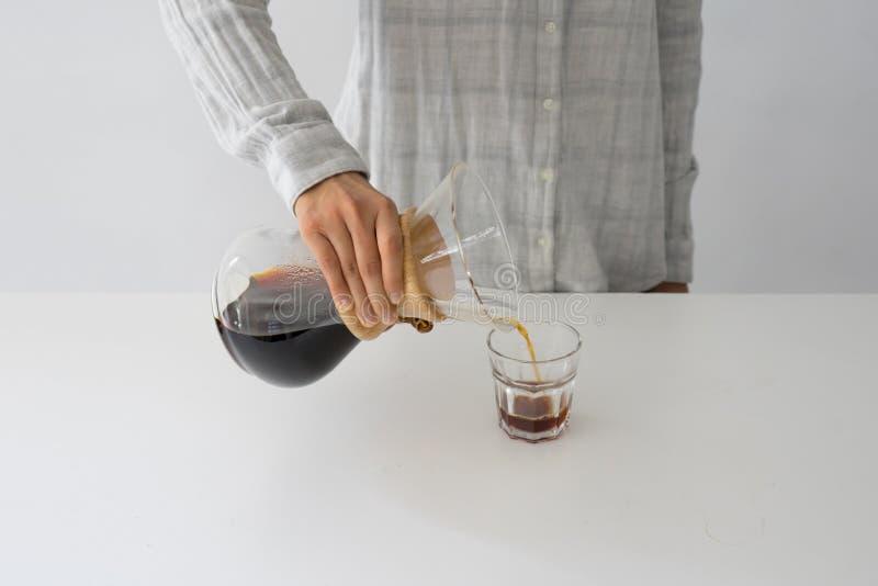 Caffè che versa al vetro sulla parete bianca e sulla Tabella bianca immagini stock libere da diritti