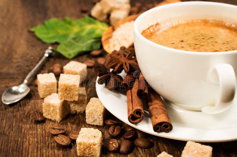 Caffè con cannella, anice stellato, i chicchi di caffè e lo zucchero di canna fotografia stock
