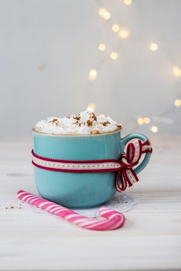 Caffè con crema in tazza ceramica con un nastro e caramella di natale sul fondo del bokeh fotografia stock libera da diritti