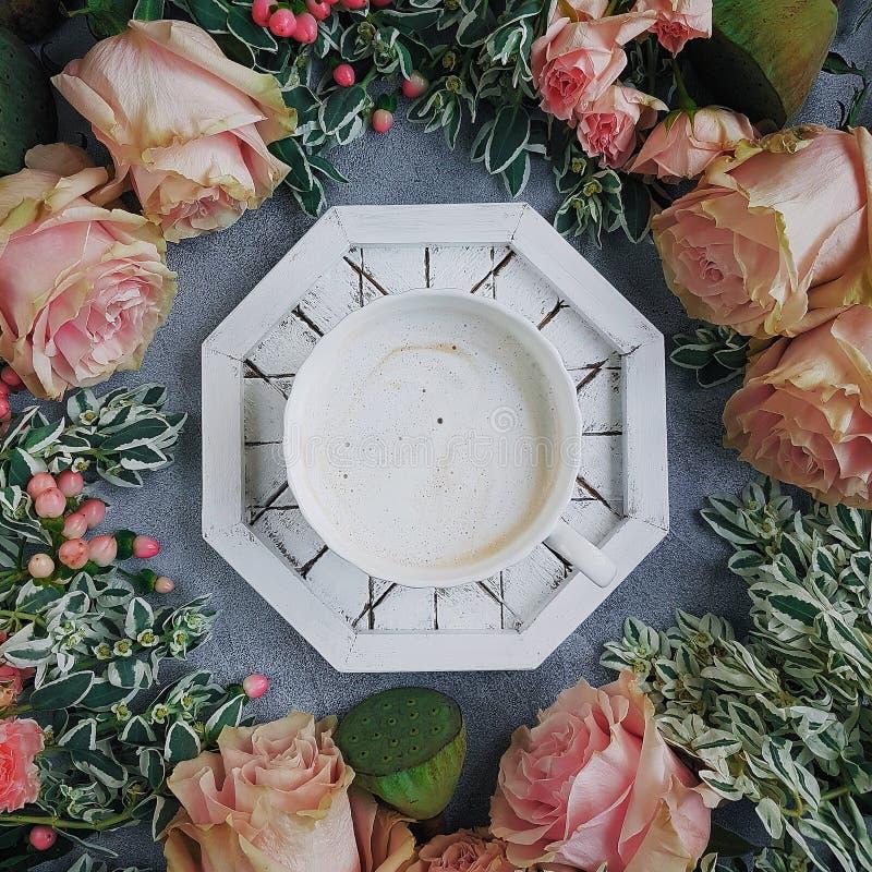 Caffè con i fiori, lo stile del blog, Flatlay, fondo leggero, Floristics, le rose delicate, il loto ed i verdi fotografie stock libere da diritti