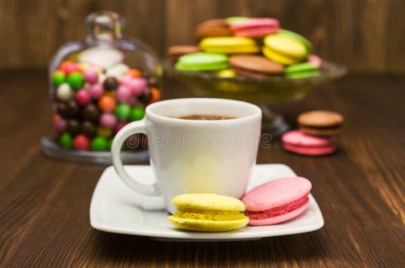 Caffè con i maccheroni variopinti e le caramelle fotografia stock