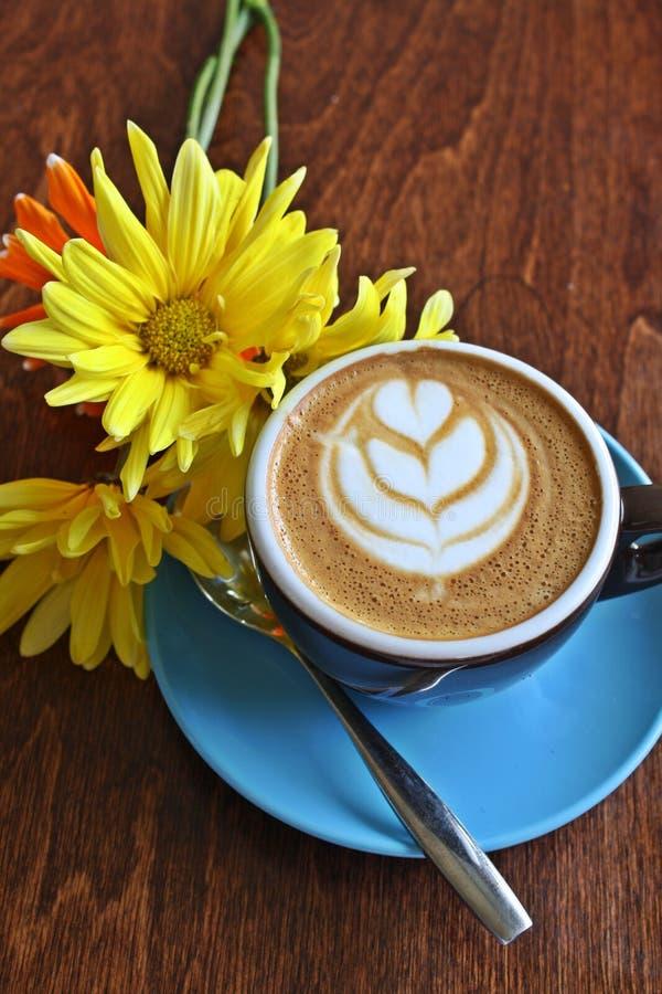 Caffè con l'immagine ed i fiori del cuore. fotografia stock