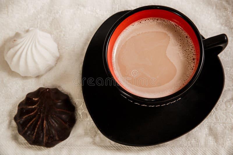 Caffè con latte in tazza alla moda nera e due caramelle gommosa e molle immagine stock