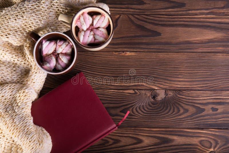 Caffè con le caramelle gommosa e molle, la sciarpa di lana ed il libro su un fondo di legno Cioccolato caldo di inverno Concetto  immagini stock