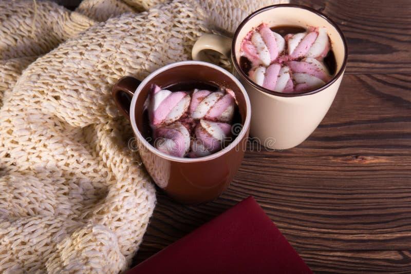 Caffè con le caramelle gommosa e molle, la sciarpa di lana ed il libro su un fondo di legno Cioccolato caldo di inverno Concetto  fotografia stock