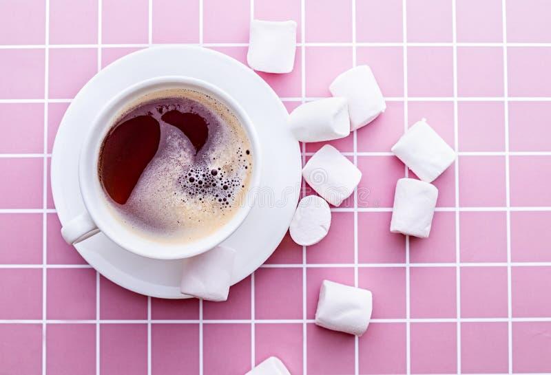 Caffè con le caramelle gommosa e molle in una tazza bianca sulla vista superiore del fondo di rosa fotografia stock