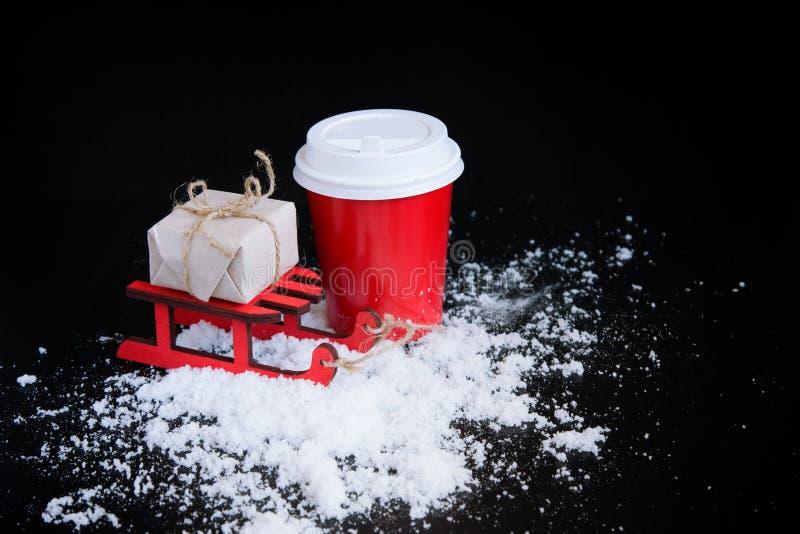 Caffè da andare in tazza, in slitta e nel regalo di Natale rossi immagini stock