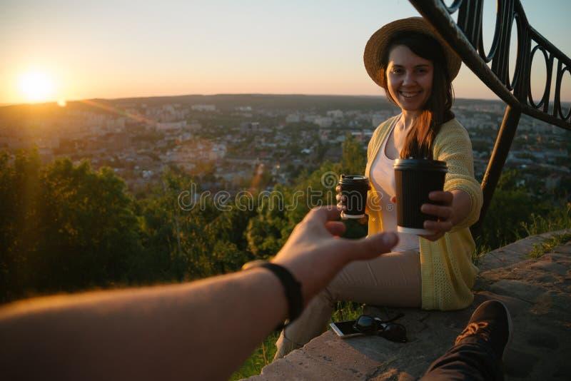 Caffè dante femminile da equipaggiare mentre essi che si siedono sulla collina su alba immagine stock libera da diritti