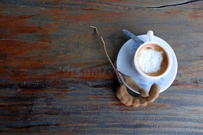 Caffè del cappuccino nella tazza bianca con il cucchiaio di caffè e tamarindo sulla tavola di legno fotografia stock libera da diritti