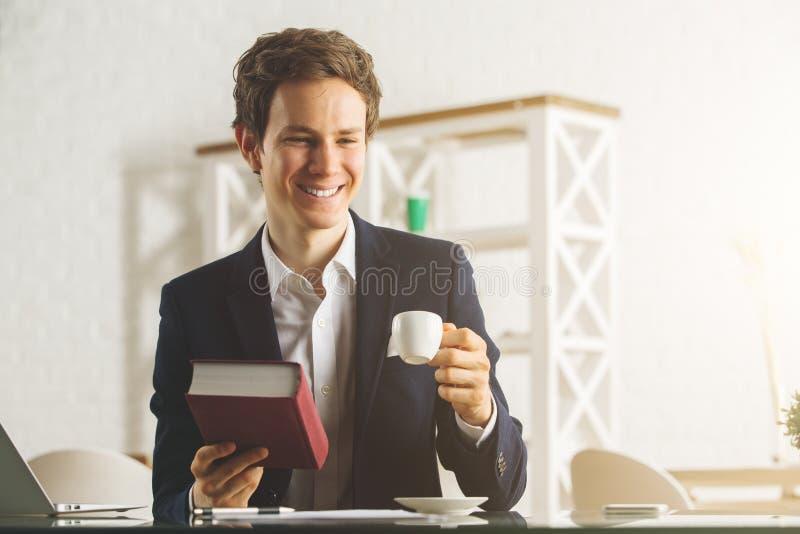 Caffè del signore attraente e libro di lettura beventi immagine stock libera da diritti