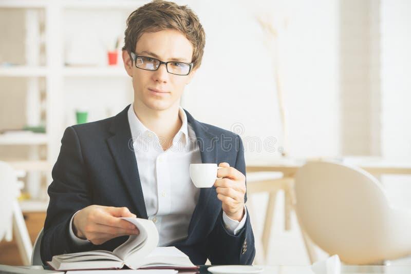 Caffè dell'uomo attraente e libro di lettura beventi immagini stock libere da diritti