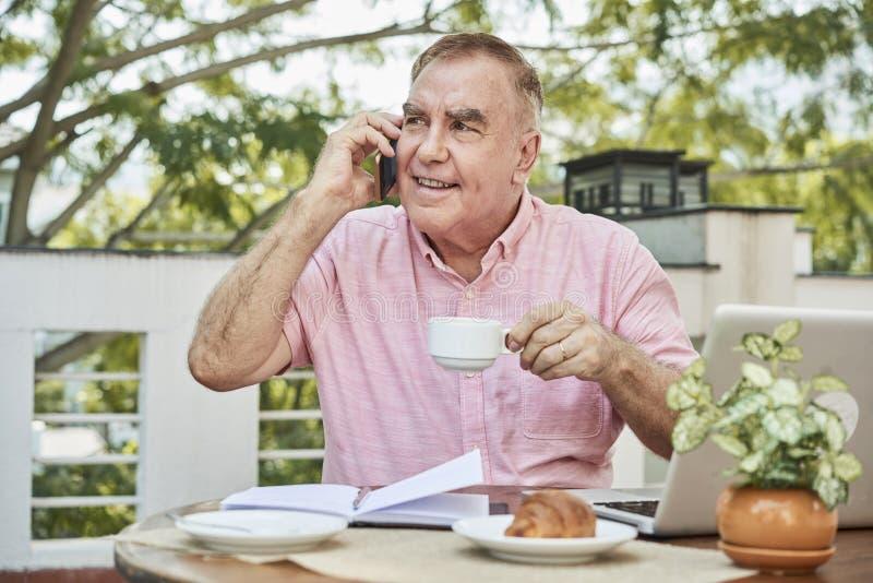 Caffè dell'uomo d'affari e telefono beventi rivolgersi immagini stock libere da diritti