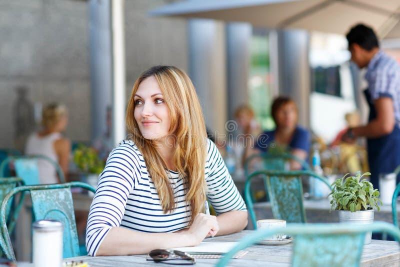 Caffè della donna e note beventi di scrittura in caffè fotografia stock
