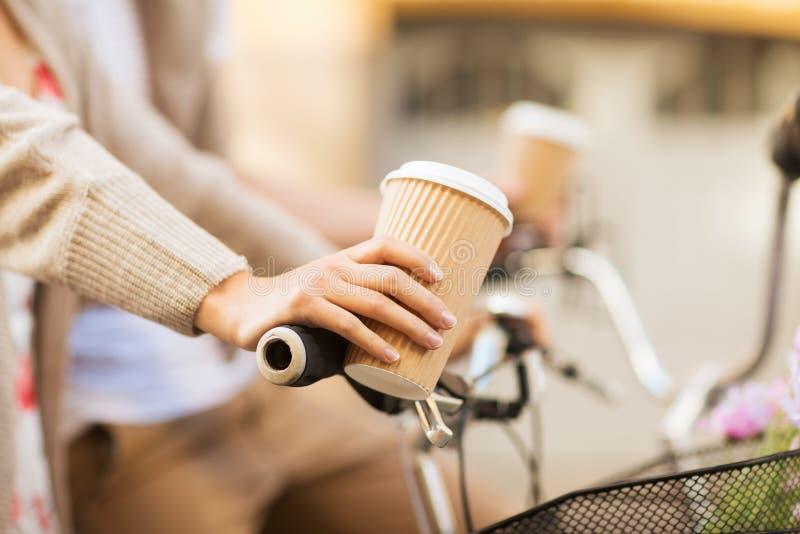 Caffè della tenuta della mano della donna e bicicletta di guida fotografie stock libere da diritti