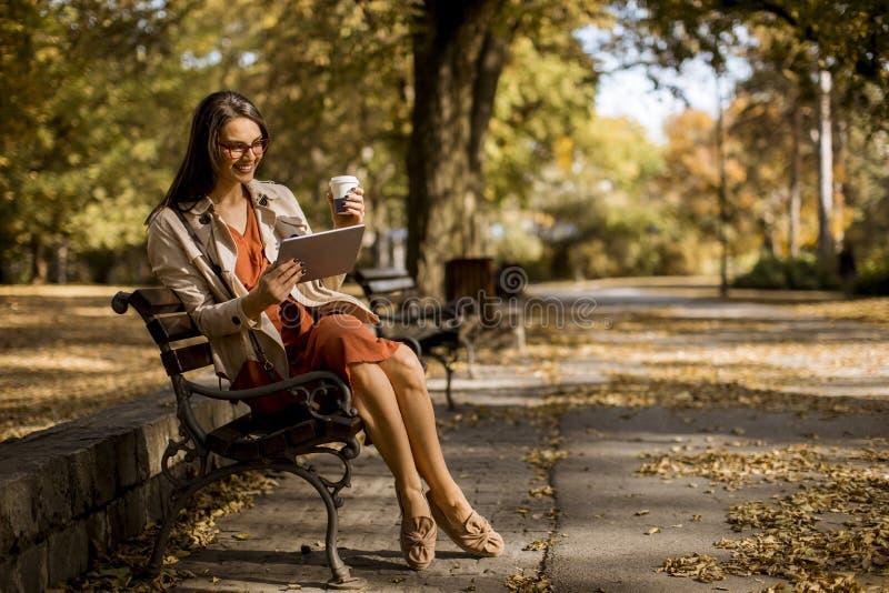 Caffè delle bevande della giovane donna ed utilizzare compressa digitale nel parco fotografia stock