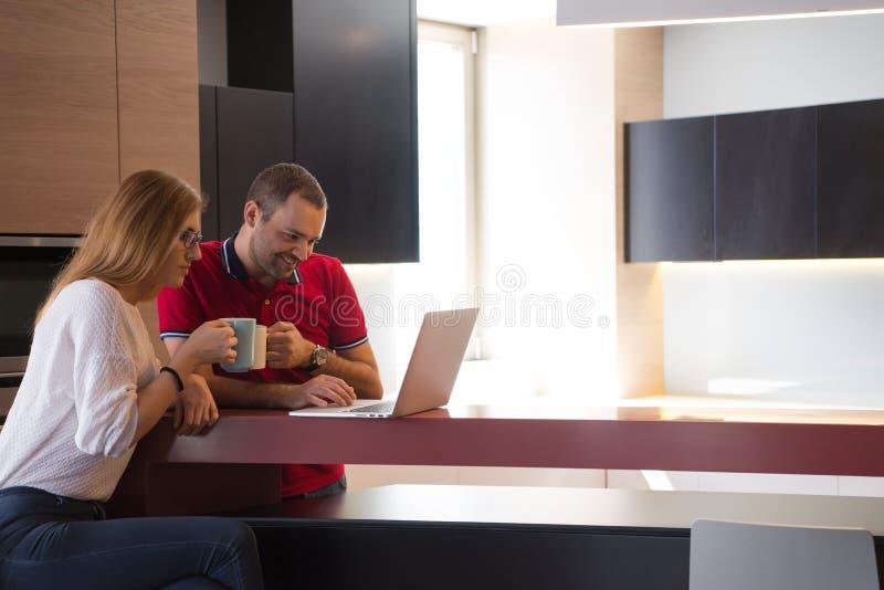 Caffè delle coppie ed usando computer portatile beventi a casa immagine stock