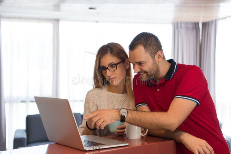 Caffè delle coppie ed usando computer portatile beventi a casa fotografia stock libera da diritti