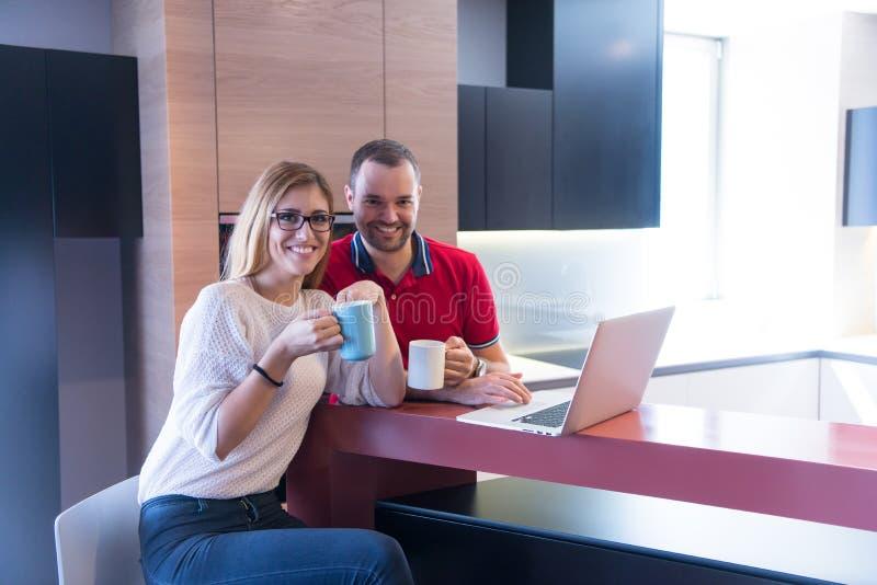 Caffè delle coppie ed usando computer portatile beventi a casa immagini stock