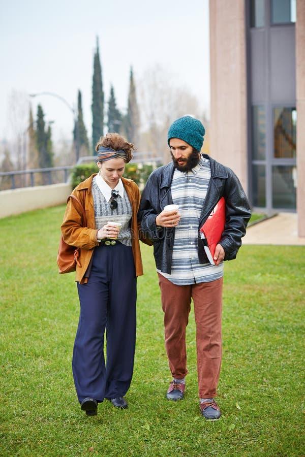 Caffè di conversazione e bevente delle coppie dei pantaloni a vita bassa per andare fotografia stock libera da diritti