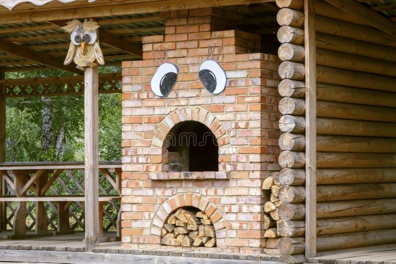 Caffè di estate nel villaggio Una capanna rurale per un picnic nella foresta e una stufa del mattone per la cottura sul fuoco immagini stock libere da diritti