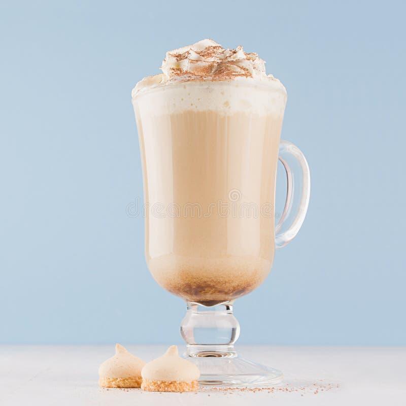 Caffè di Macchiato con panna montata, cioccolato in polvere, i biscotti in calice trasparente su fondo blu pastello ed il legno  fotografie stock libere da diritti