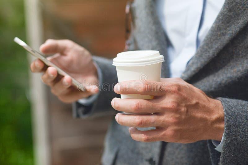 Caffè di mattina della tenuta della mano e telefono della lettura fotografia stock