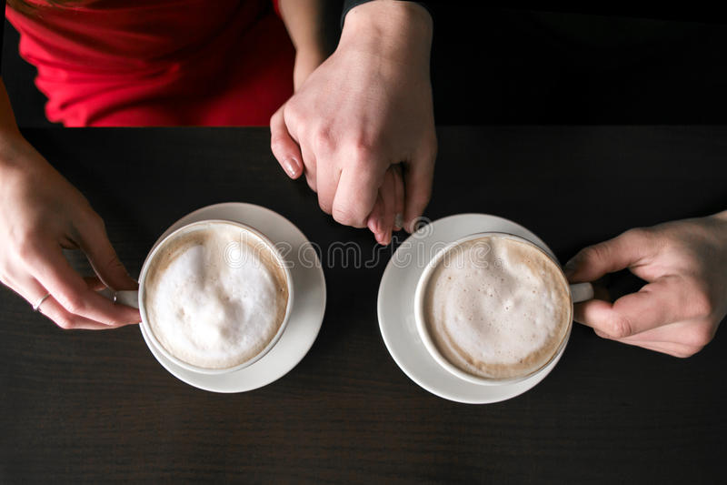 Caffè di seduta e bevente delle giovani coppie al ristorante del caffè due tazze con caffè sono sulla tavola Mani dell'uomo e del immagine stock libera da diritti