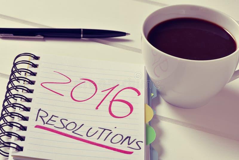 Caffè e blocco note con le risoluzioni del testo 2016 fotografia stock