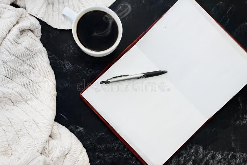 Caffè e libro aperto del maglione immagini stock