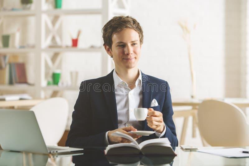 Caffè e libro di lettura beventi maschii attraenti immagini stock