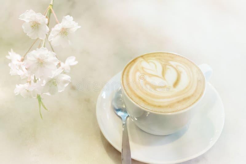 Caffè e sakura caldi del latte fotografia stock