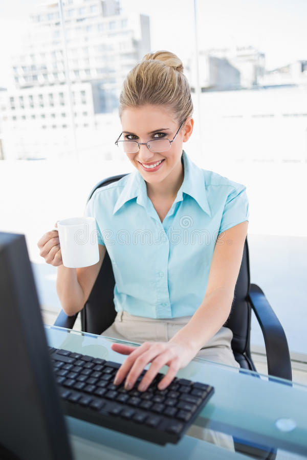 Caffè elegante sorridente della tenuta della donna di affari mentre lavorando fotografia stock