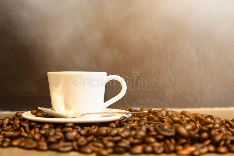 Caffè espresso in una tazza di caffè e dei chicchi di caffè caldi sul fondo nero della parete in un negozio del caffè, sul caffè  fotografia stock