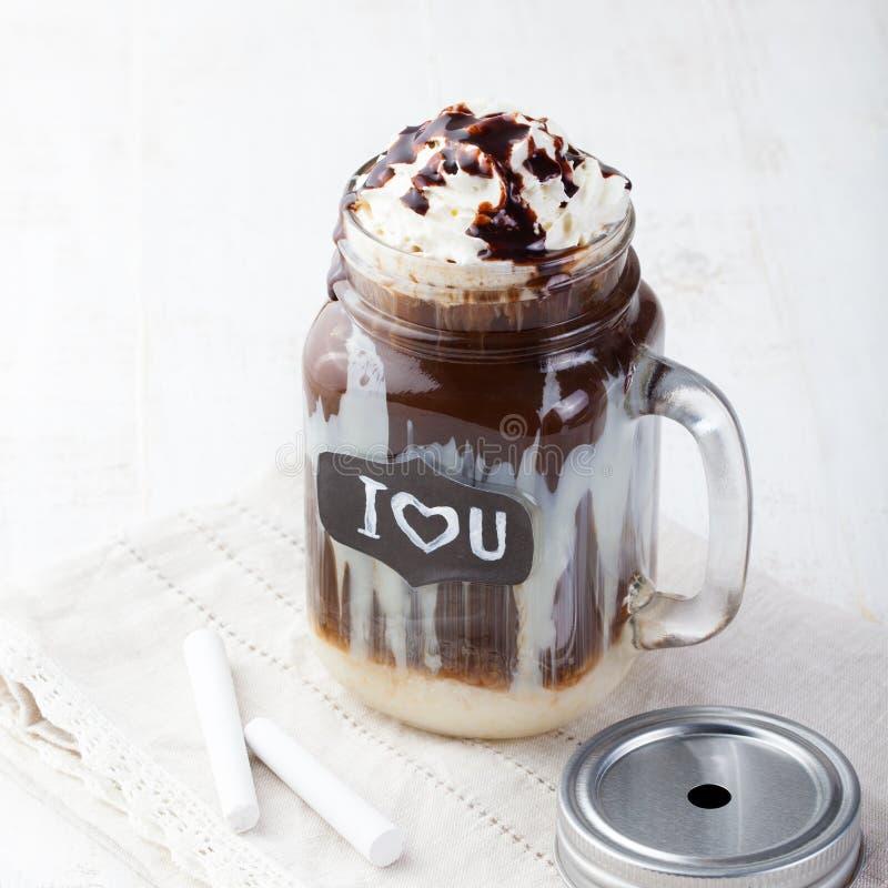Caffè freddo ghiacciato, frapuccino con panna montata e sciroppo di cioccolato in barattolo con la lavagna ti amo su una tavola b immagine stock