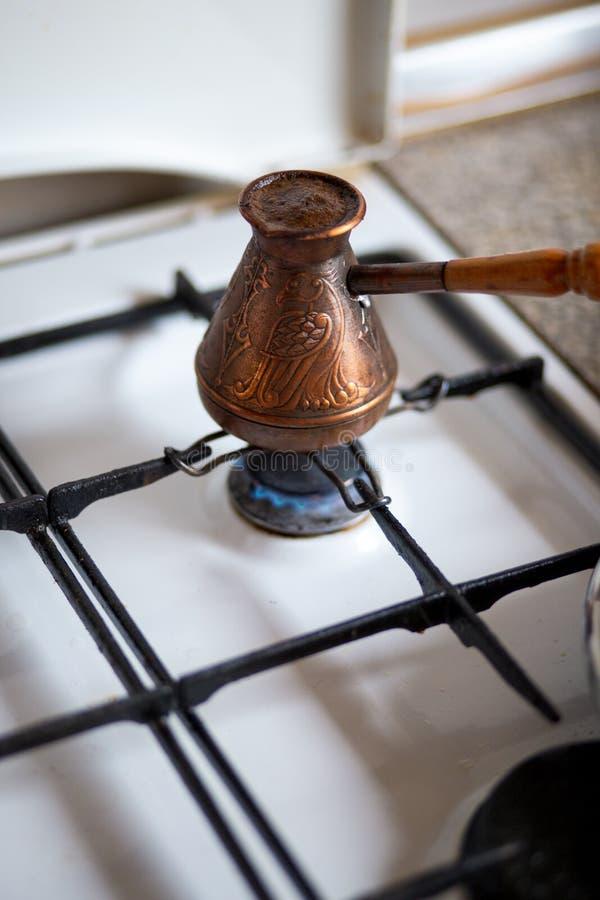 Caffè fresco con il cardamomo bollito nel cezve - caffè preparato in un cezve di rame su una stufa di gas in cucina tipica accogl immagini stock libere da diritti