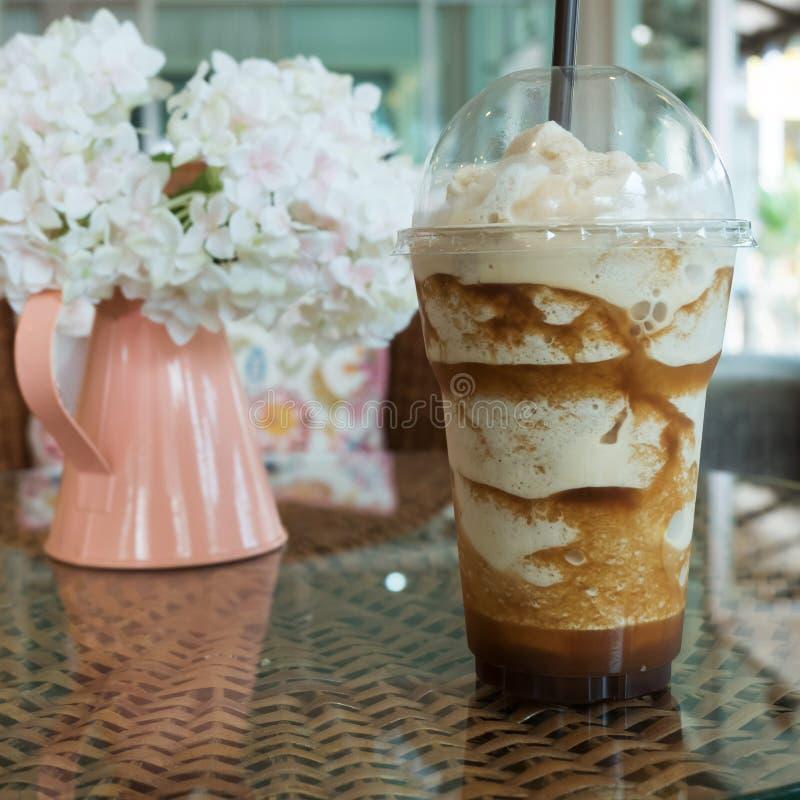 caffè ghiacciato del frappe in tazza di plastica messa sulla tavola immagini stock libere da diritti