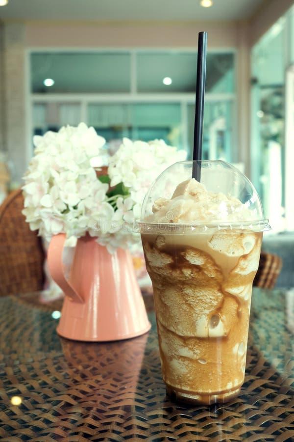 Caffè ghiacciato del frappe in tazza di plastica messa sulla tavola del tessuto del rattan fotografia stock