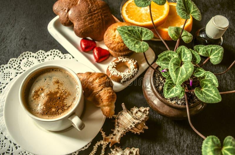 Caffè istantaneo con le pasticcerie ed il cioccolato, fette arancio circa il ciclamino fotografia stock