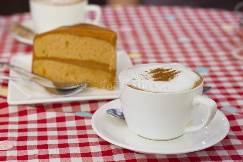 Caffè macchiato sulla Tabella rossa e bianca del panno del plaid del percalle immagini stock