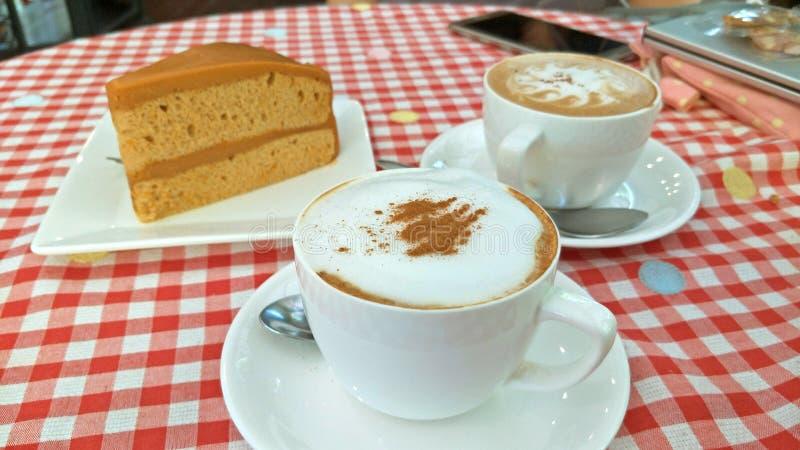 Caffè macchiato sulla Tabella rossa e bianca del panno del plaid del percalle fotografia stock libera da diritti