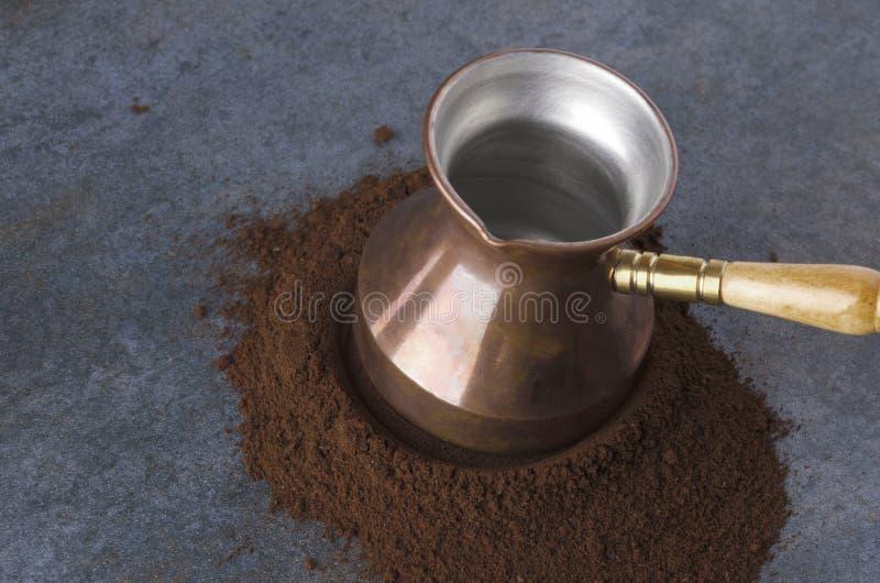 Caffè macinato, caffettiera turca, tavola grigia, primo piano immagine stock