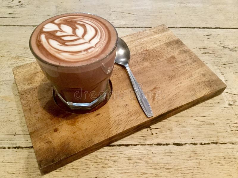 Hot Cocoa Latte. Delicious drink. A caffè mocha, on a wooden table with spoon, also called mocaccino, is a chocolate-flavored variant of a caffè latte royalty free stock photo