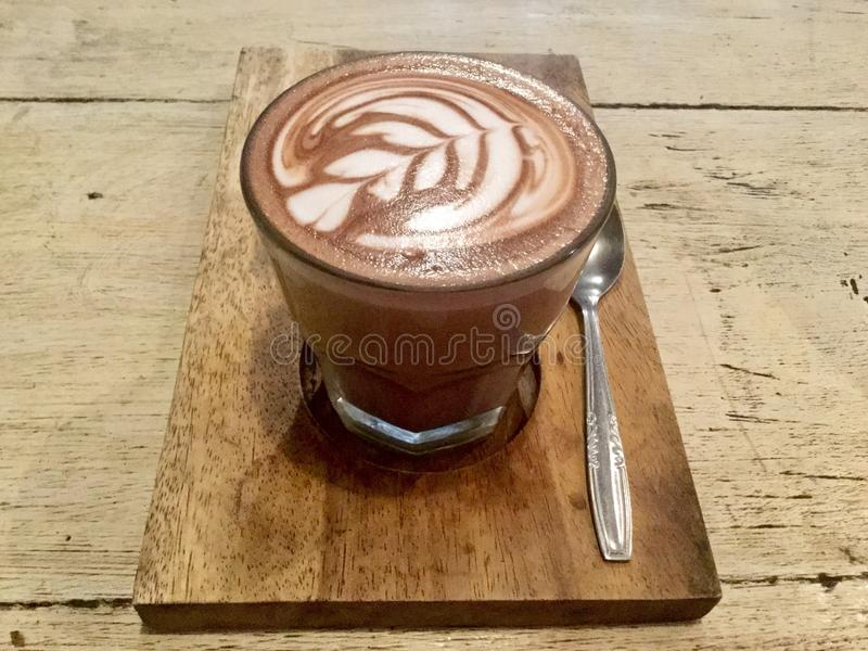 Delicious latte. Hot caffe mocha. top view. Drink. A caffè mocha, on a wooden table with spoon, also called mocaccino, is a chocolate-flavored variant of a royalty free stock image