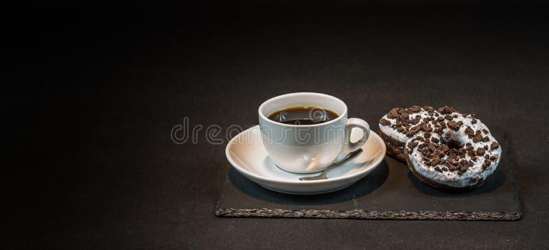 Caffè nero aromatico in una tazza bianca con la ciambella di oreo due sulla a fotografia stock