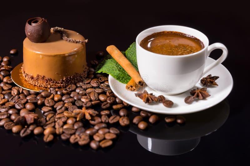 Caffè nero con il dolce ed i fagioli di cioccolato gastronomici fotografie stock