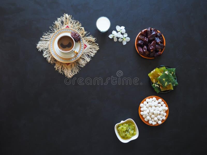 Caffè nero, latte, datteri e dolci turchi su un fondo nero Alimento dolce per il Ramadan fotografia stock libera da diritti